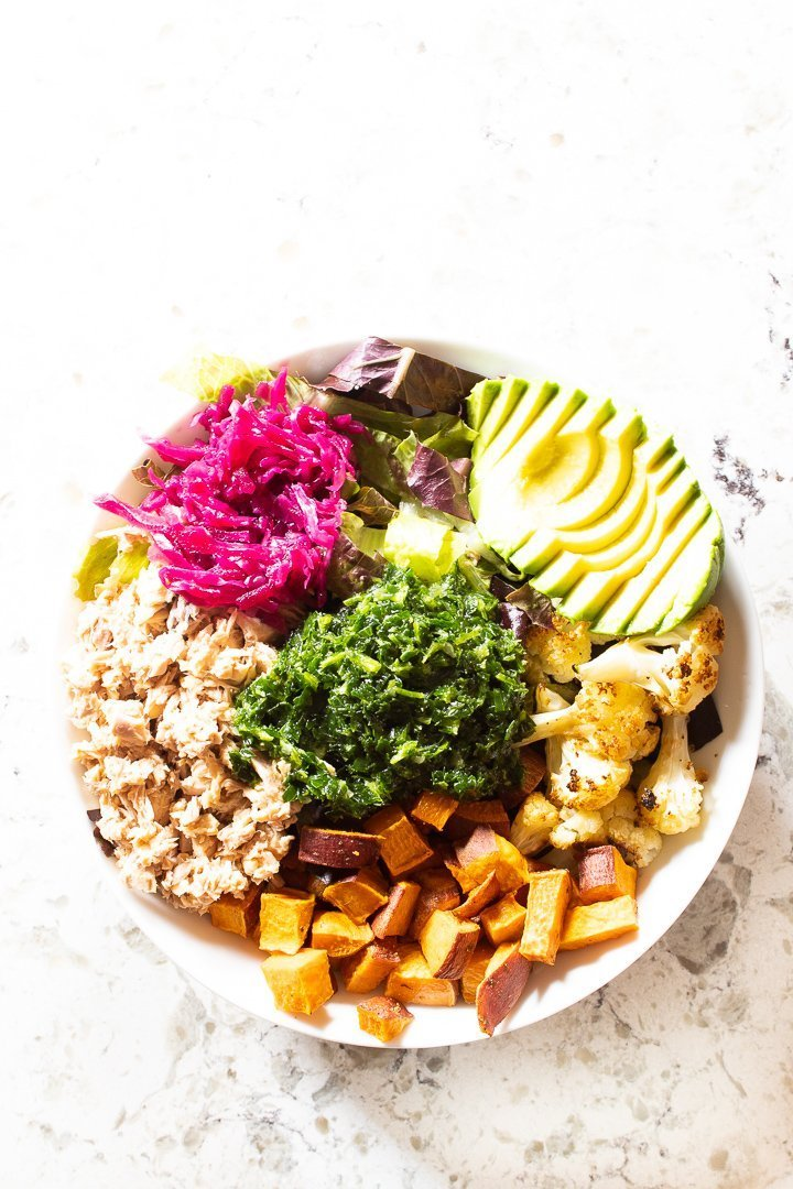 Top view of AIP Nourishing Buddha Bowl with sweet potato, cauliflower, chopped romaine, salmon, fermented kraut, avocado and arugula pesto.