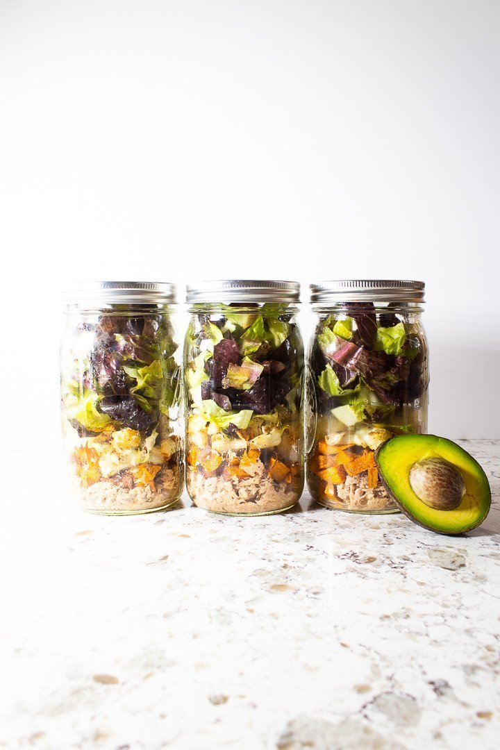 Mason jar salads of AIP Nourishing Buddha Bowl with sweet potato, cauliflower, chopped romaine, salmon, fermented kraut, avocado and arugula pesto.
