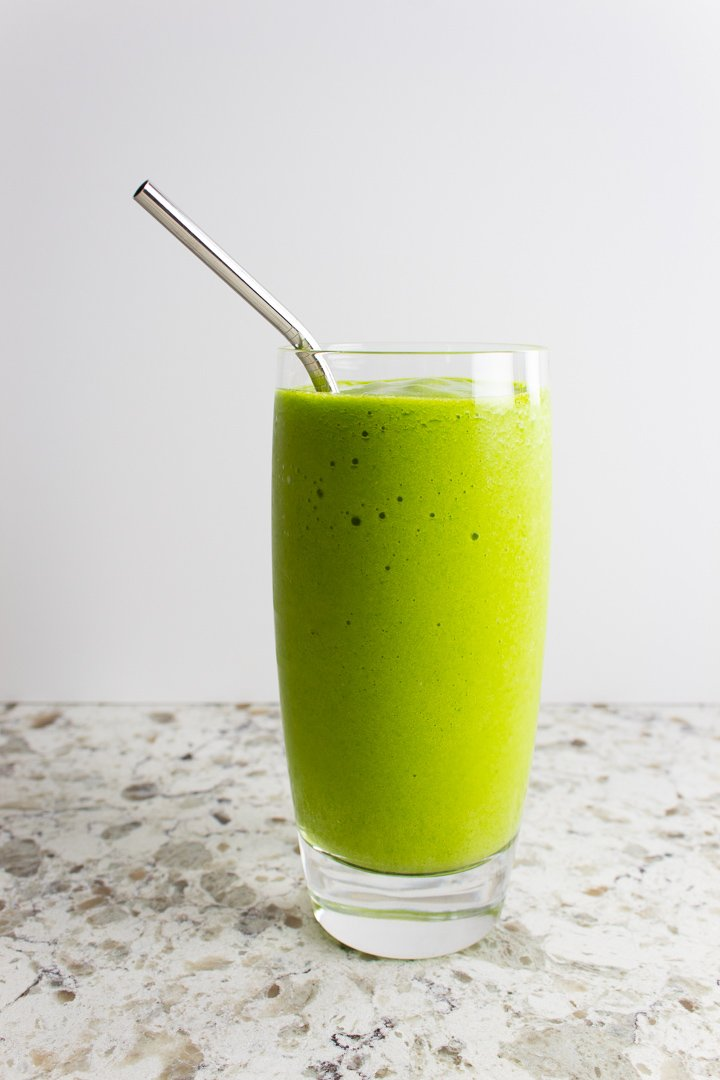 Mango Ginger Green Smoothie in a tall glass with a stainless steel straw.